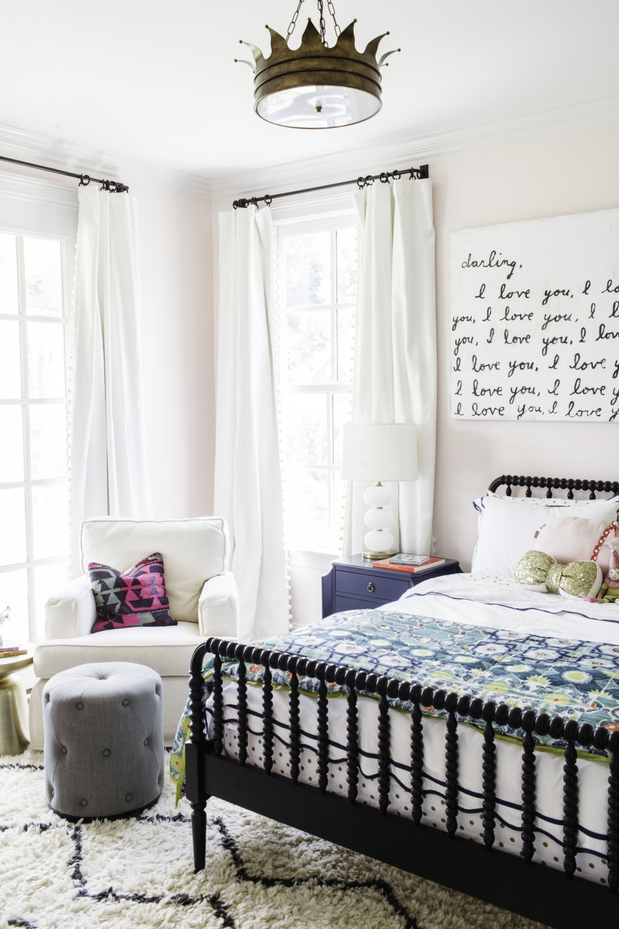 Child's bedroom with light pink walls, black bed and patterned rug