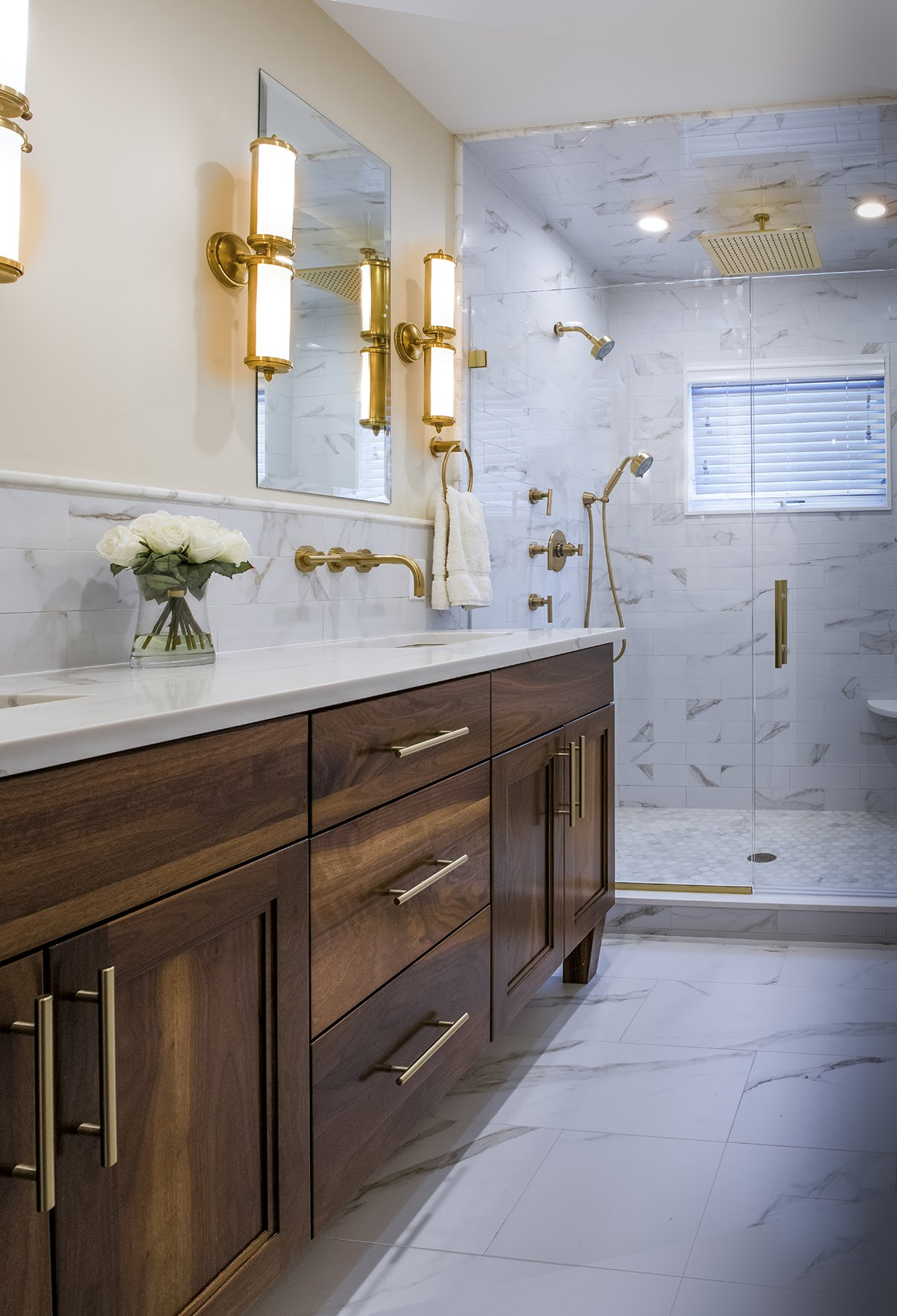 Modern marble bathroom with sconces above the sink