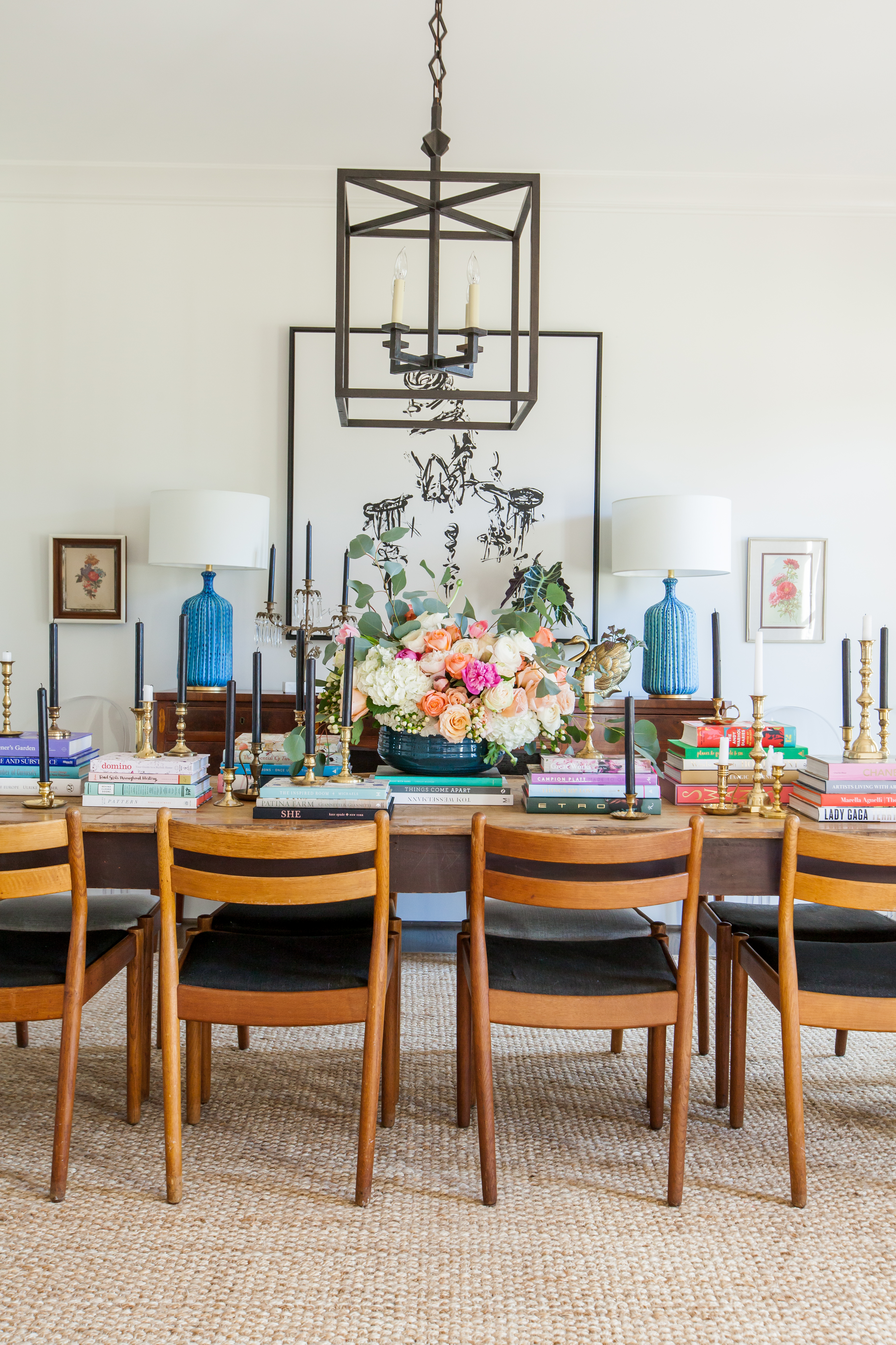 Wooden dining table with wooden chairs decorated with colorful books and flowers
