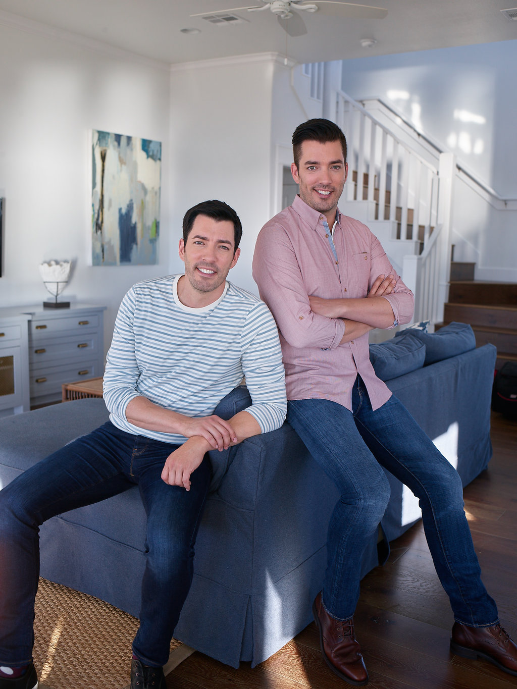 Jonathan and Drew Scott sitting on a couch